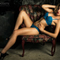 Sexy blond woman in blue lingerie reclining on chair.